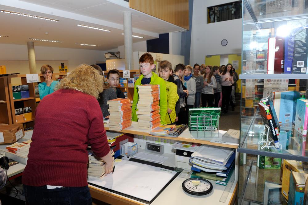 Schüler und Schülerinnen leihen sich Bücher in der Mediotheke.
