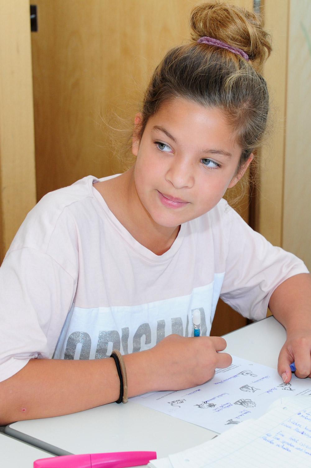 Eine Schülerin bearbeitet Aufgaben im Deutschunterricht