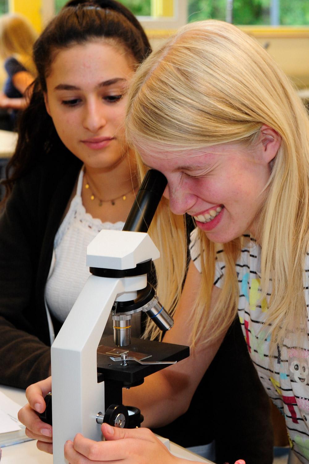 Zwei Schülerinnen arbeiten an einem Mikroskop im Nawi-Unterricht