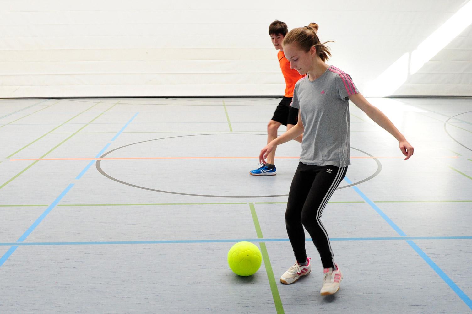 Schüler und Schülerinnen der Mittelstufe spielen Fußball im Sportunterricht