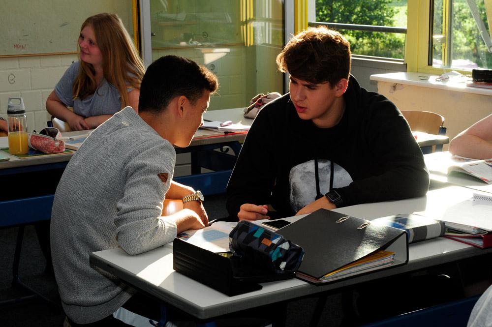 Zwei Schüler lernen Französisch und unterhalten sich miteinander