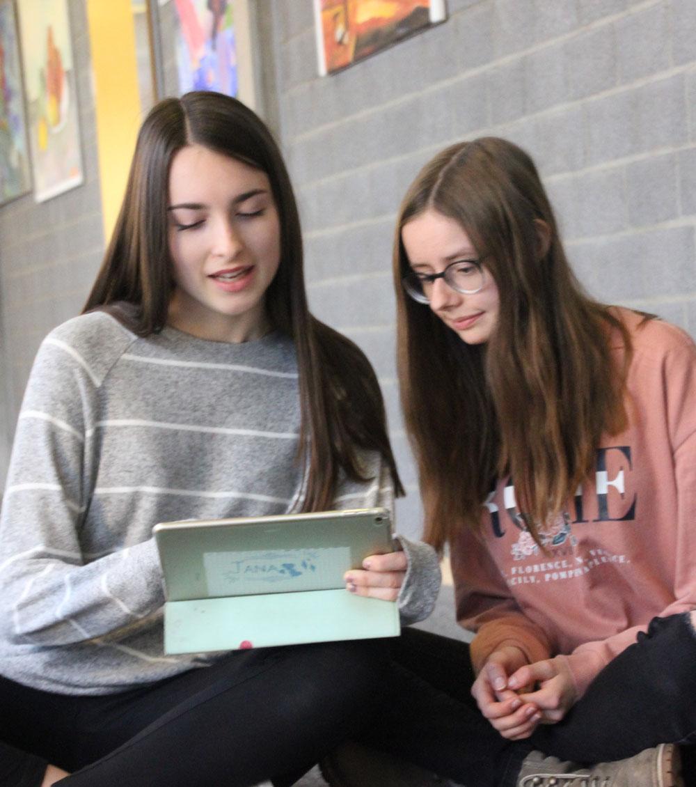Zwei Schülerinnen lernen im Unterricht mit Tablets