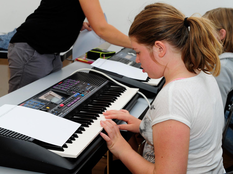 Eine Schülerin lernt im Musikunterricht Klavierspielen