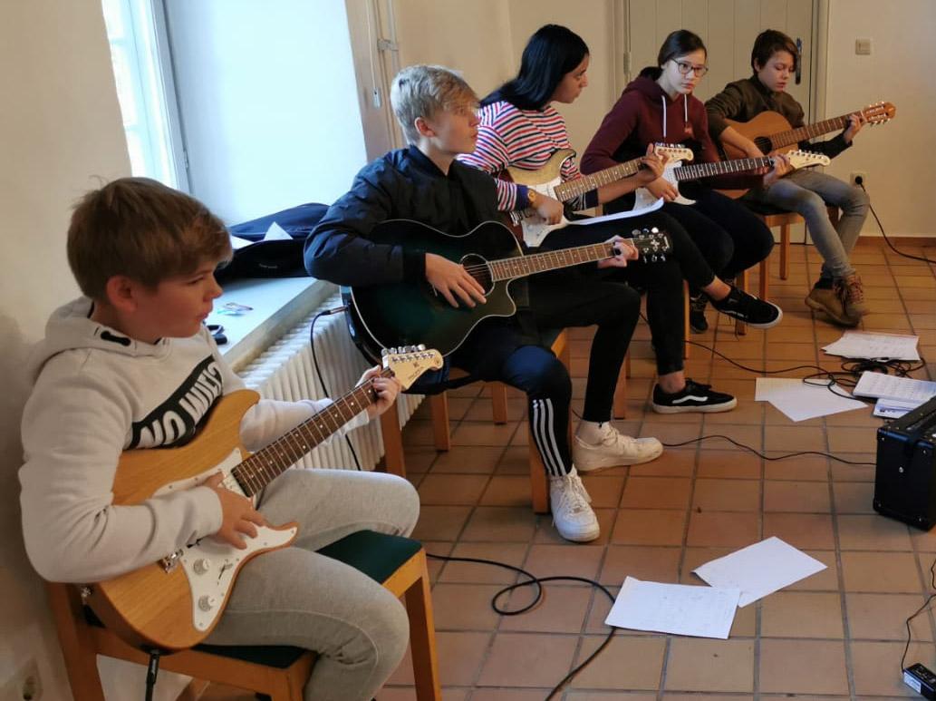 Schüler und Schülerinnen über Gitarre spielen