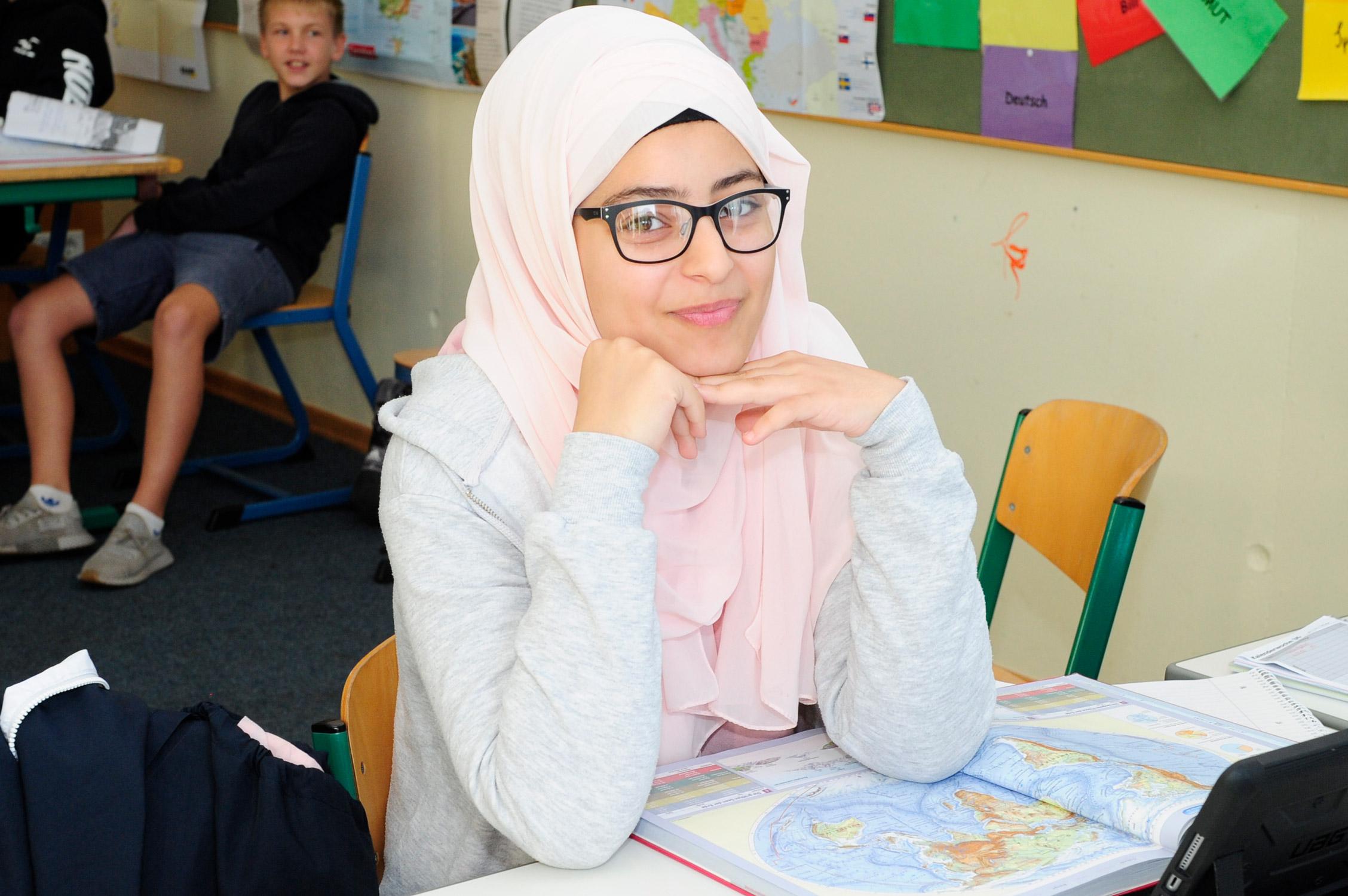 Eine Schülerin benutzt im Weltkundeunterricht einen Altas