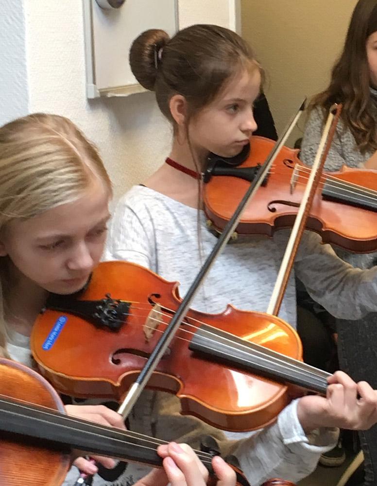 Schülerinnen spielen Geige in der Orchesterprobe