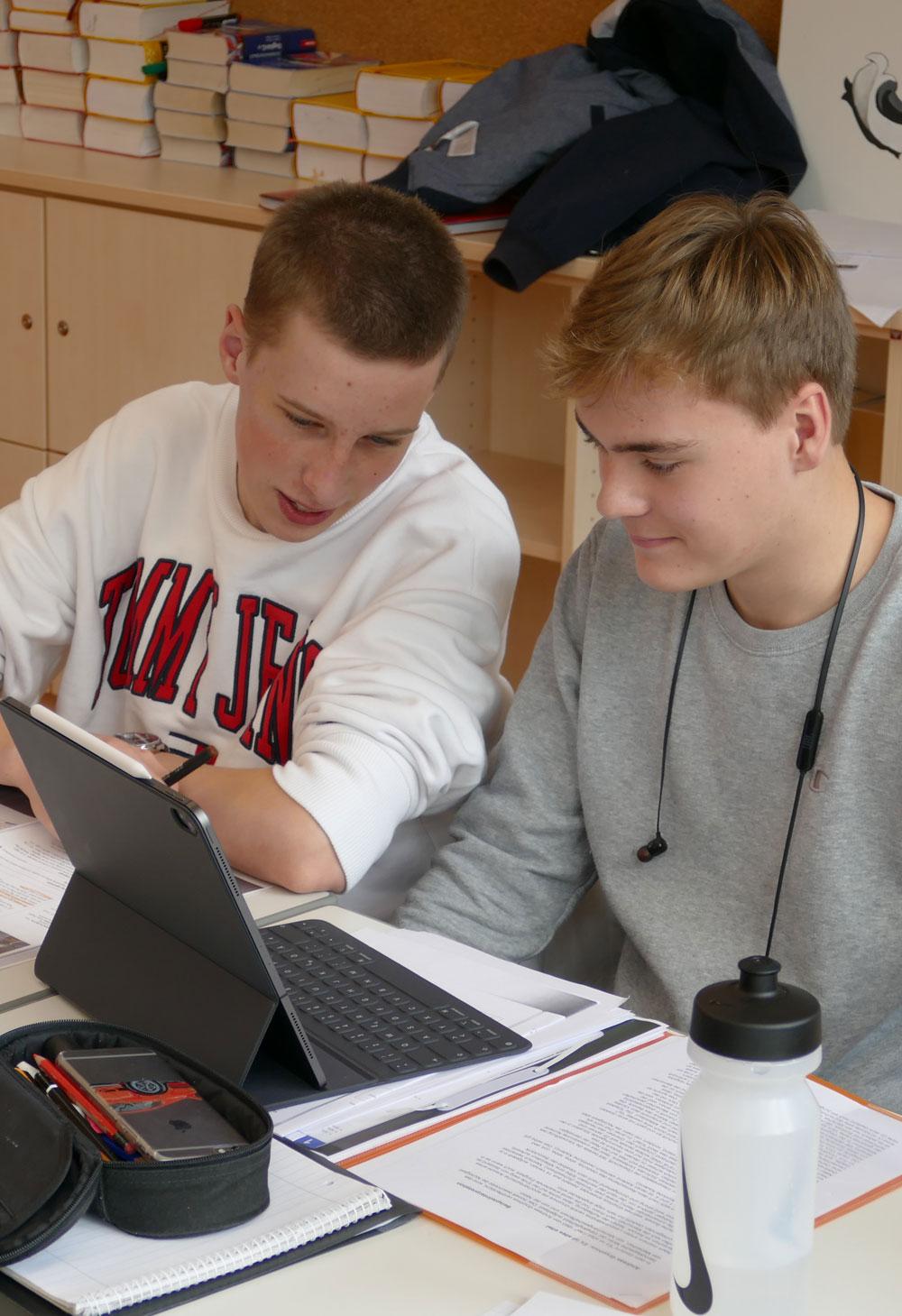 Zwei Schülerinnen auf dem Weg zum Unterricht im Fach Berufs- und Lebensorientierung mit ihren Unterlagen
