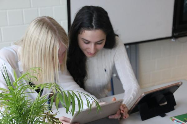 Zwei Schülerinnen arbeiten im Unterricht mit Tablets